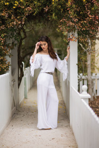 MOODY BLUES BOUTIQUE Julianne looks breathtaking in this off-the-shoulder jumpsuit with fringe detailing on the sleeves. Pair a Pink Pewter belt and cute cork wedges for a chic finish.