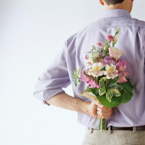 Man Holding a Bouquet of Flowers Behind His Back