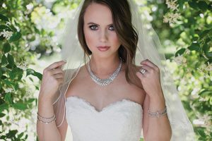 HOLLIS & COMPANY JEWELERS Diamond Bib necklace by Sethi Couture. Edwardian and Art Deco diamond earrings and bracelets. Diamond ring by Christopher Designs. Sweetheart trumpet wedding dress with beaded sash from David's Bridal.